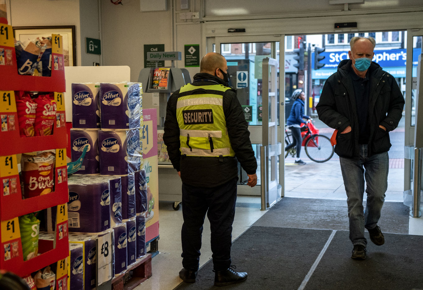 Photo of a security guard at entrance to a shop, taken from the inside looking out - Photo by Chris J Ratcliffe/Getty Images)